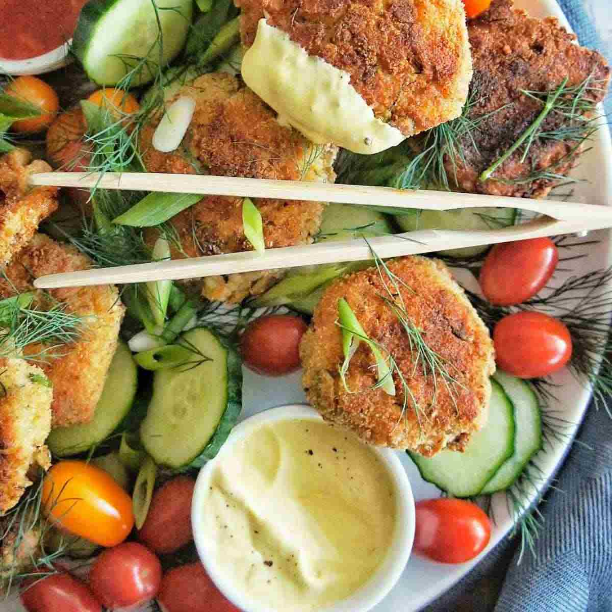 Crab cakes and salad on a large white platter with a small bowl of dipping sauce