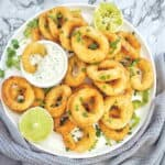 Air Fried Onion Rings on white plate with yogurt sauce