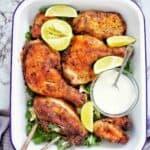 Air Fryer Jerk Chicken with herb salad and garlic yogurt sauce in white baking dish