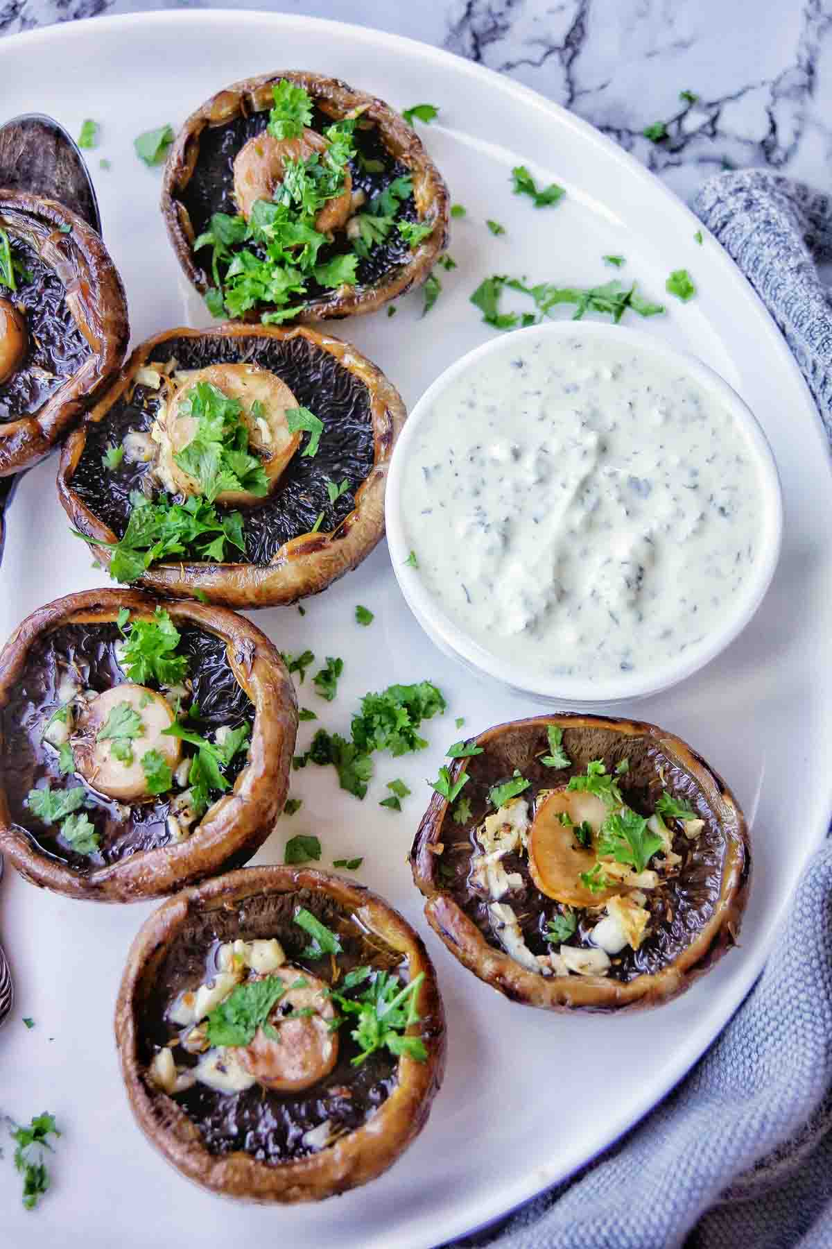 Air Fryer Portobello Mushrooms on a white plate with herb sauce