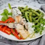 Fork flaking air fried salmon on white plate with beans and peppers