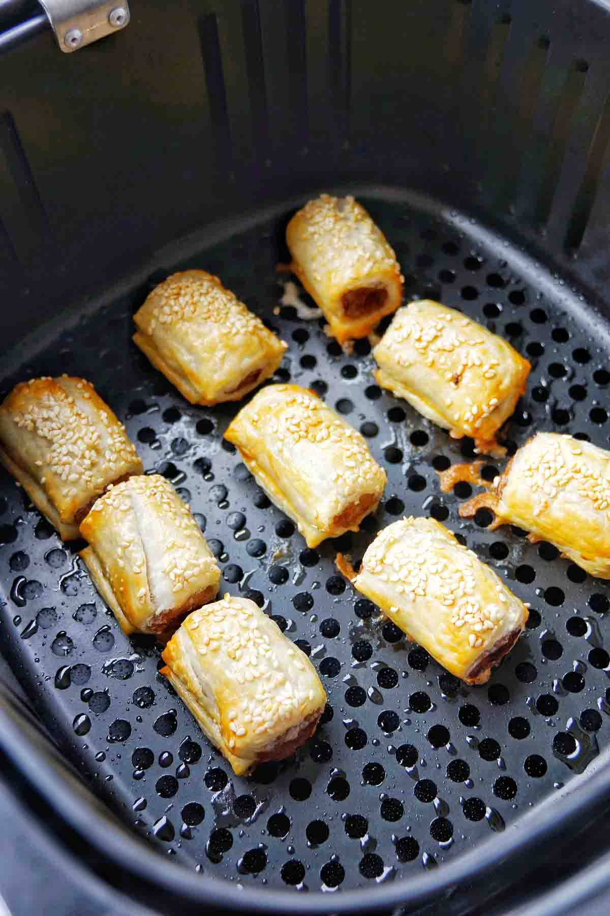 Cooked sausage rolls in basket of Air Fryer