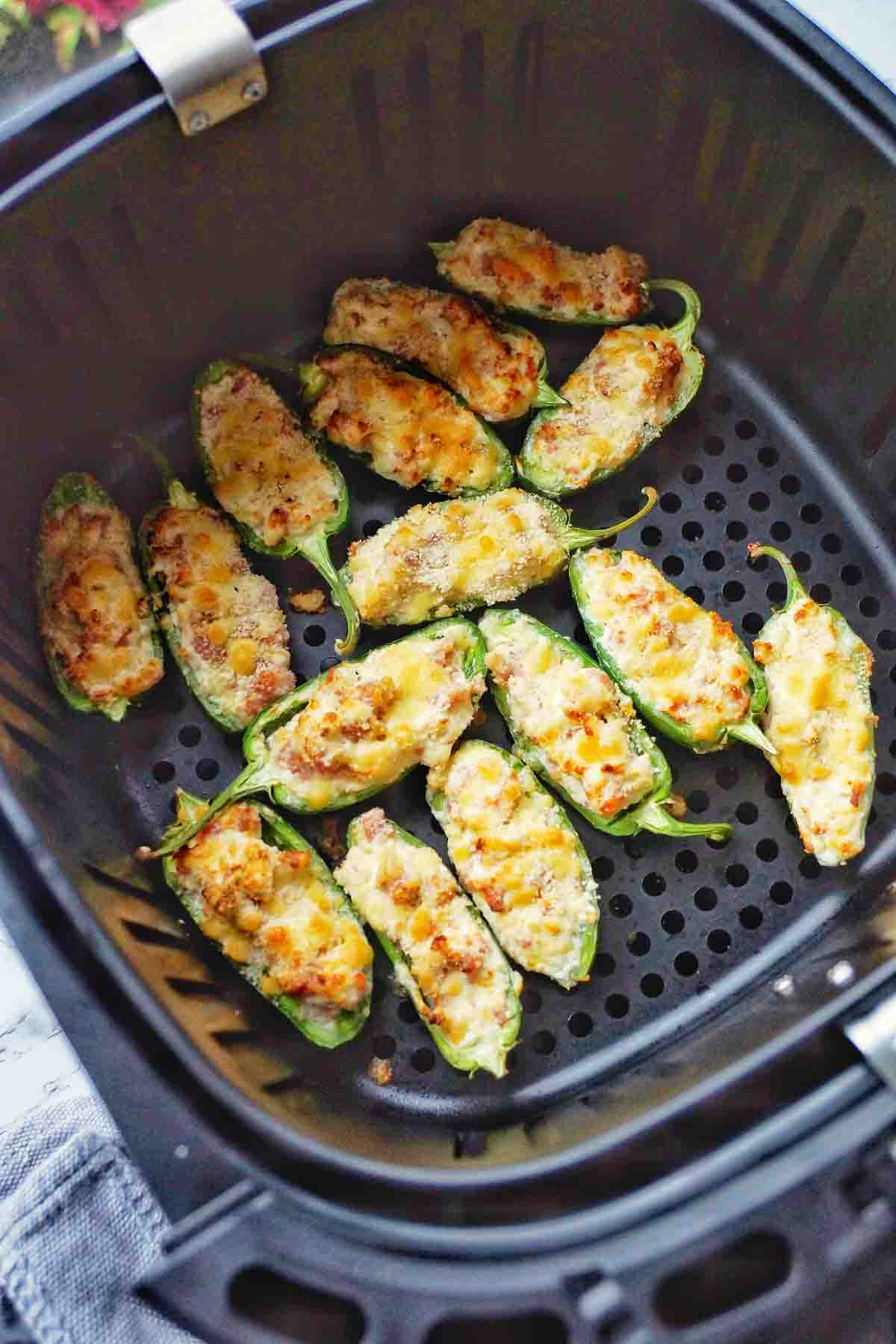 Cooked stuffed jalapenos in the basket of a air fryer
