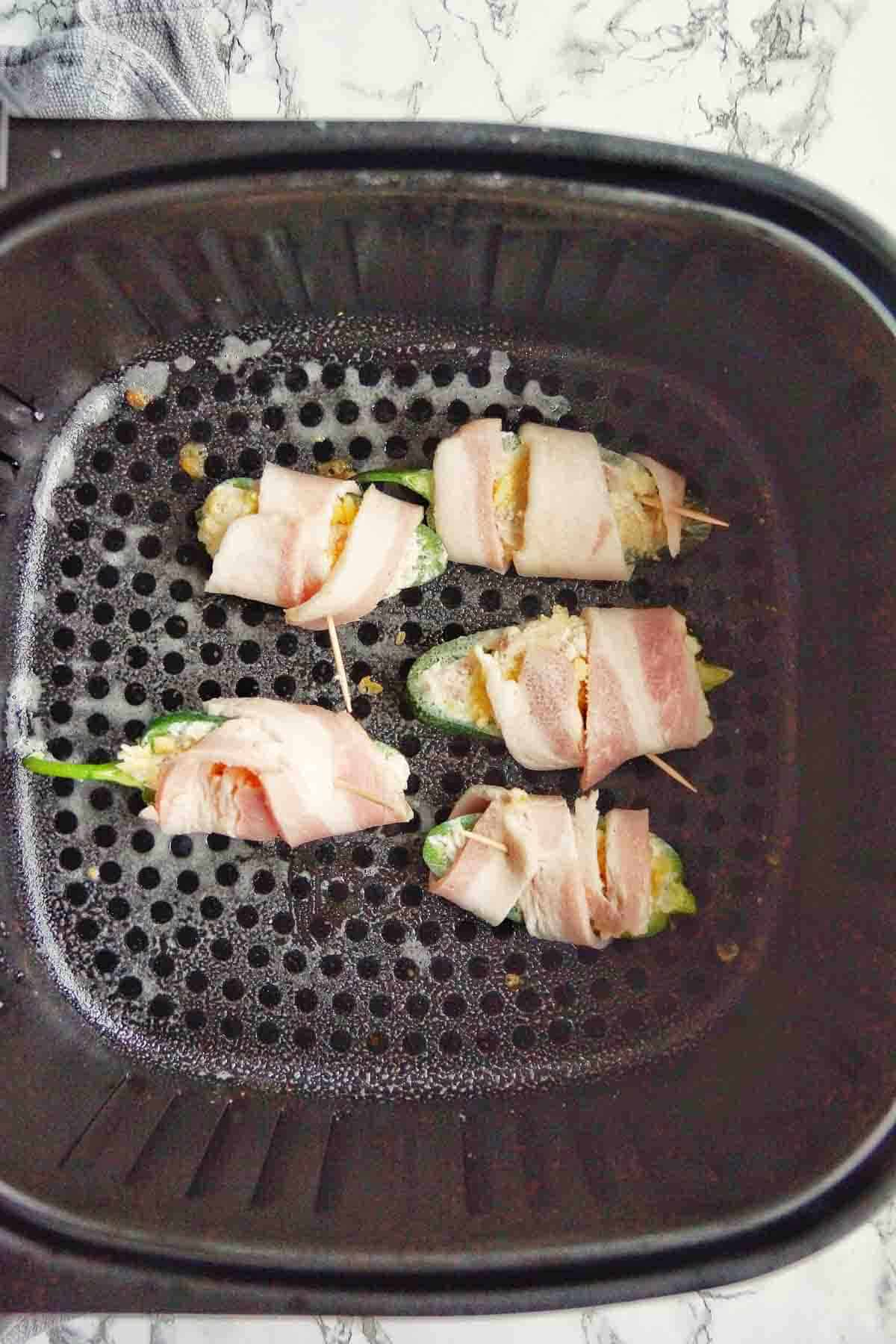 Bacon Wrapped Stuffed jalapenos in air fryer basket