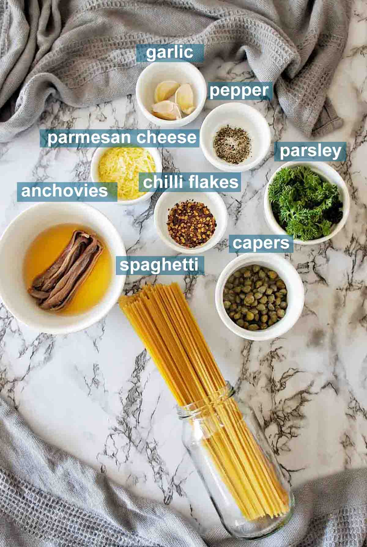Ingredients for anchovy spaghetti on marble background with text over lay