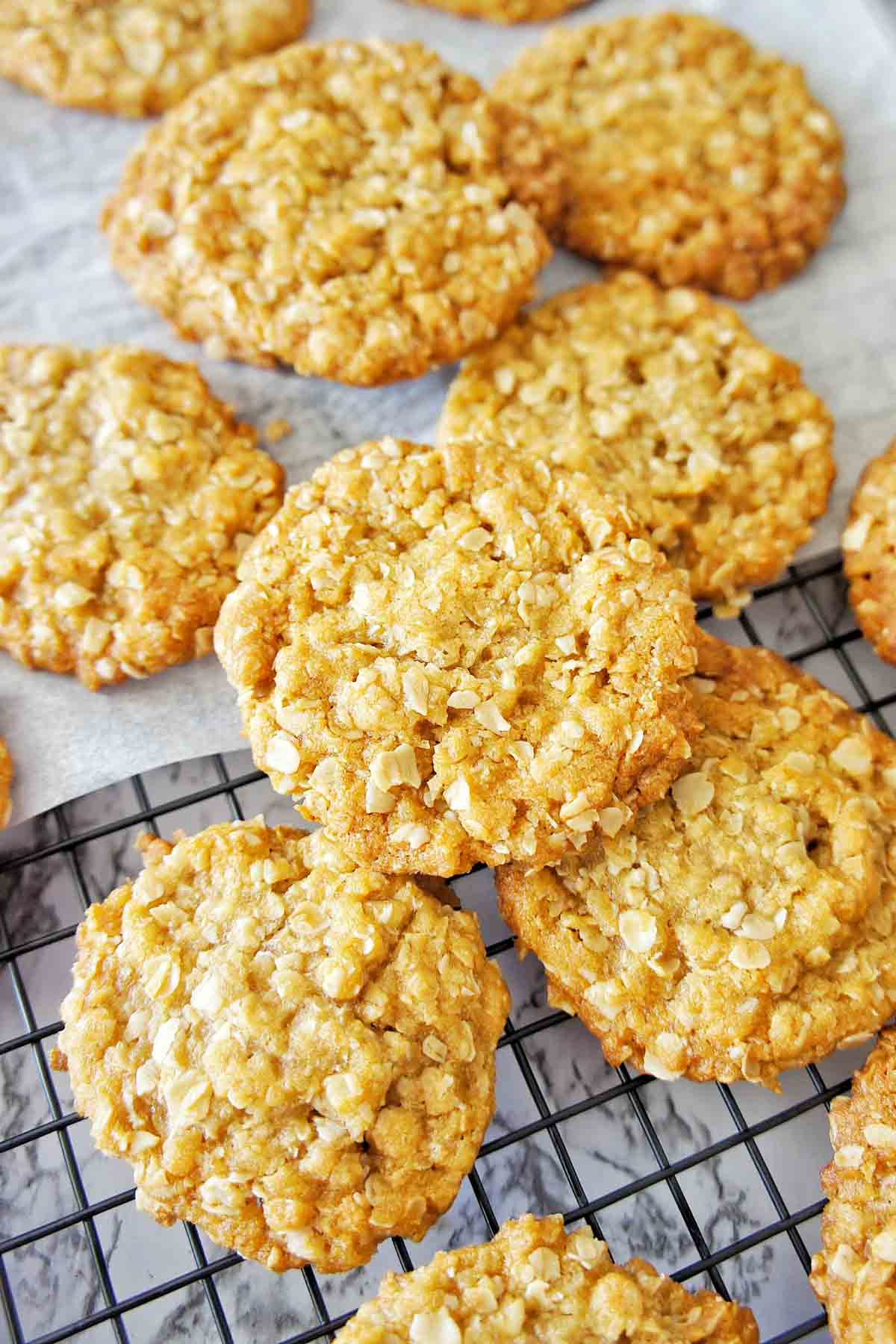 Anzac Biscuits on a black cooling tray with white baking paper underneath