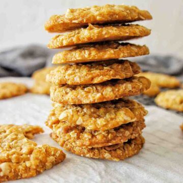 Stack of Anzac Biscuits on white baking paper