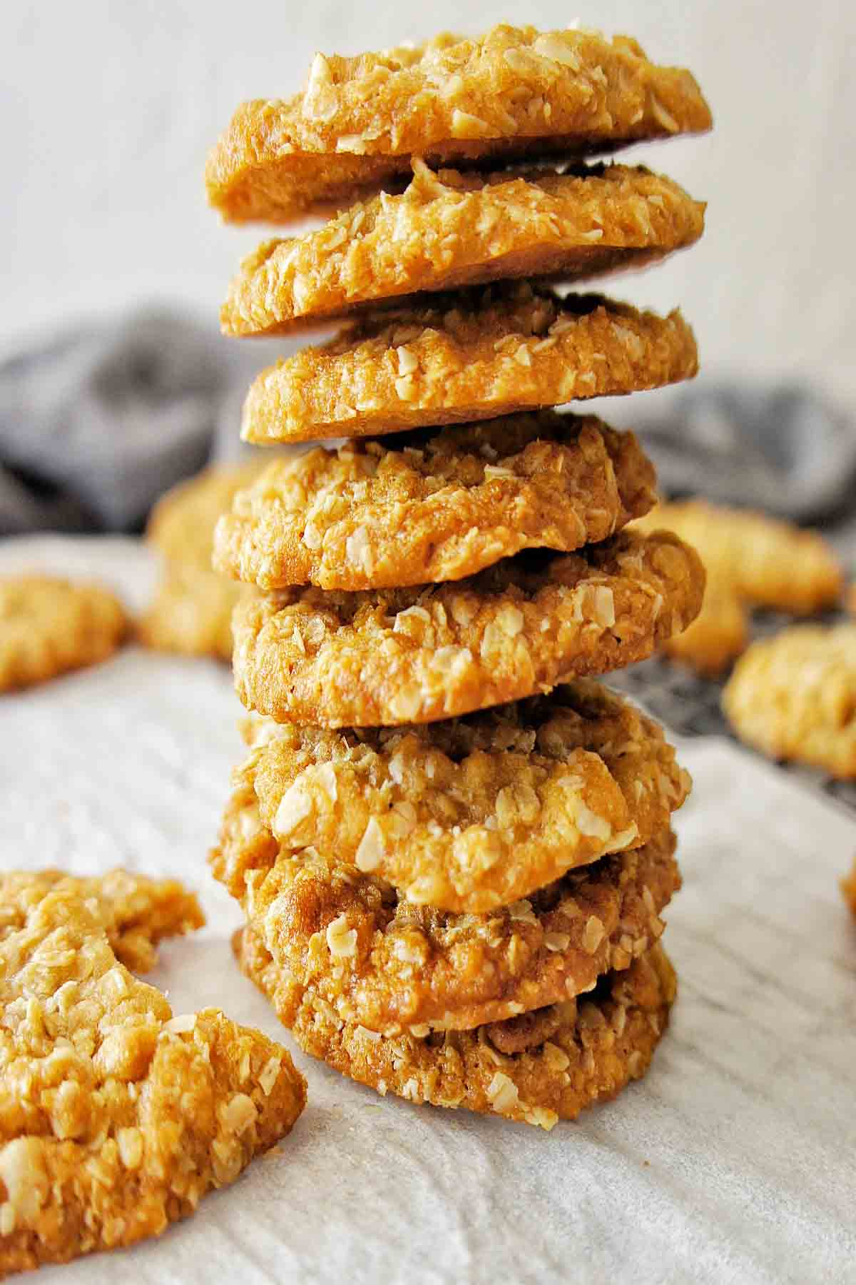 Anzac Biscuits stacked high on white baking paper