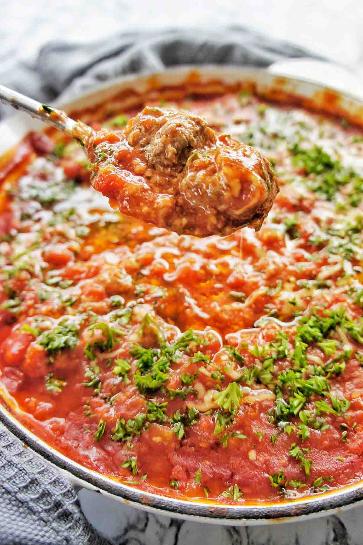 Spoon holding meatballs above a skillet of cooked Italian meatballs