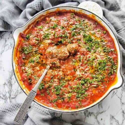 Baked Meatballs in Sauce in a white skillet with spoon out to the left