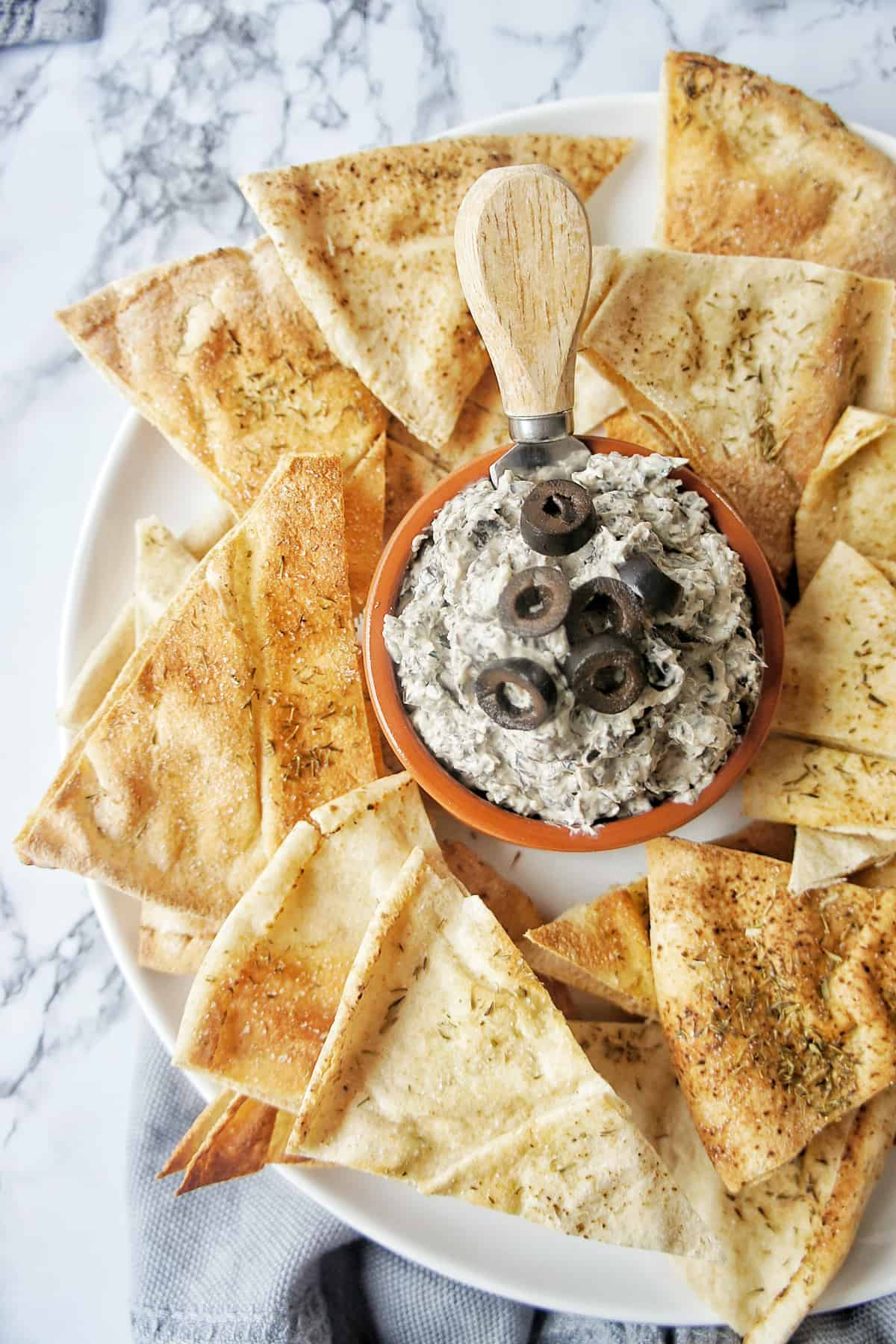 Black Olive Dip on plate with wholewheat pita chips