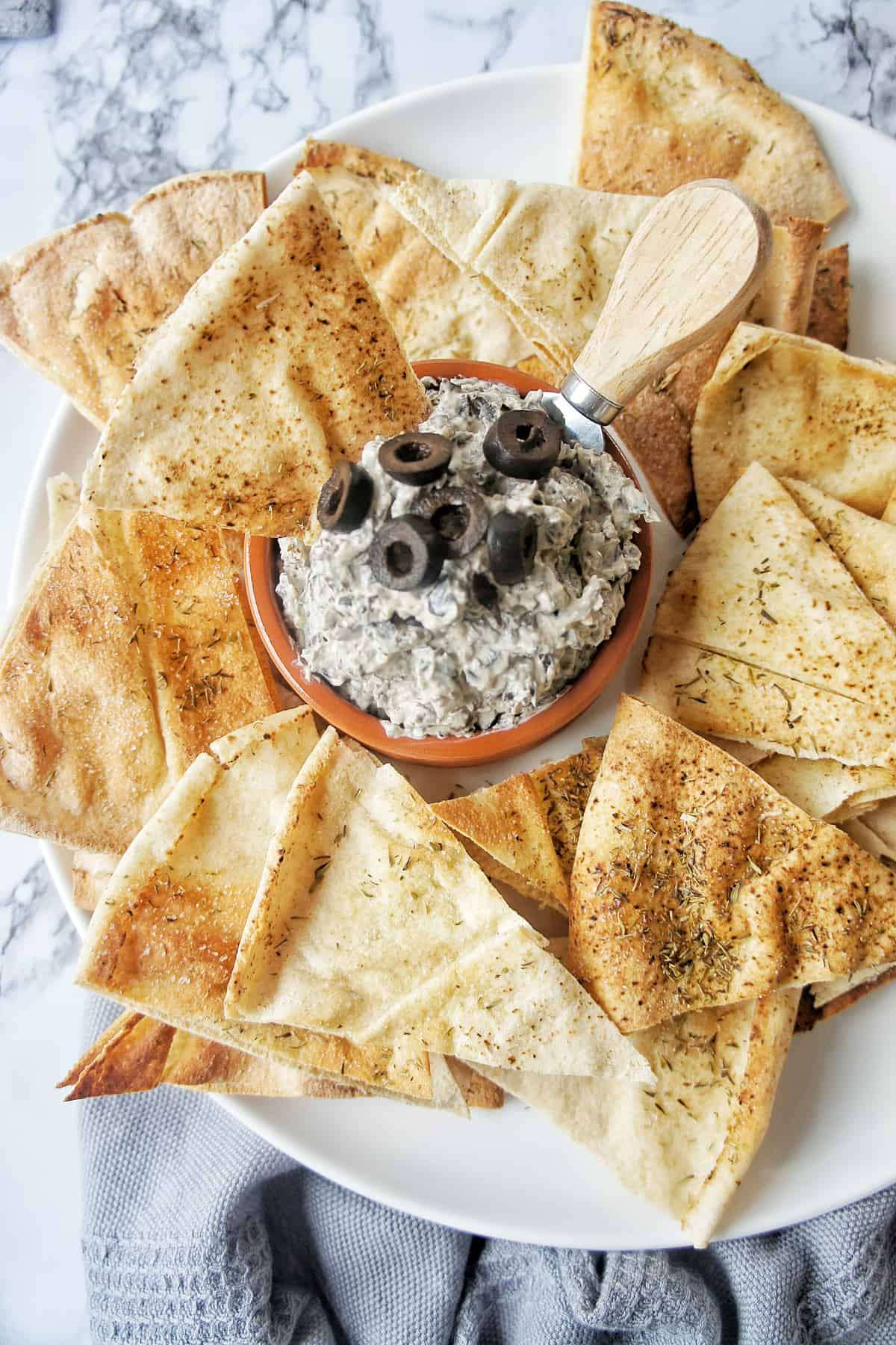 Black Olive Dip on white plate with pita chips