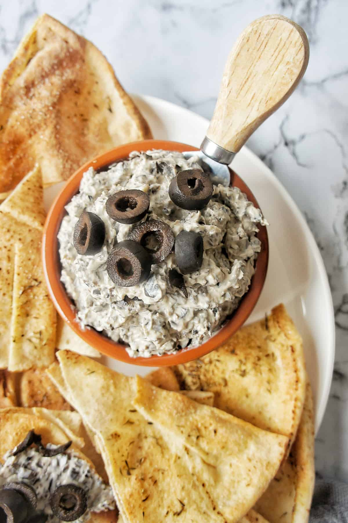 Black Olive Dip in bowl on plate with pita chips