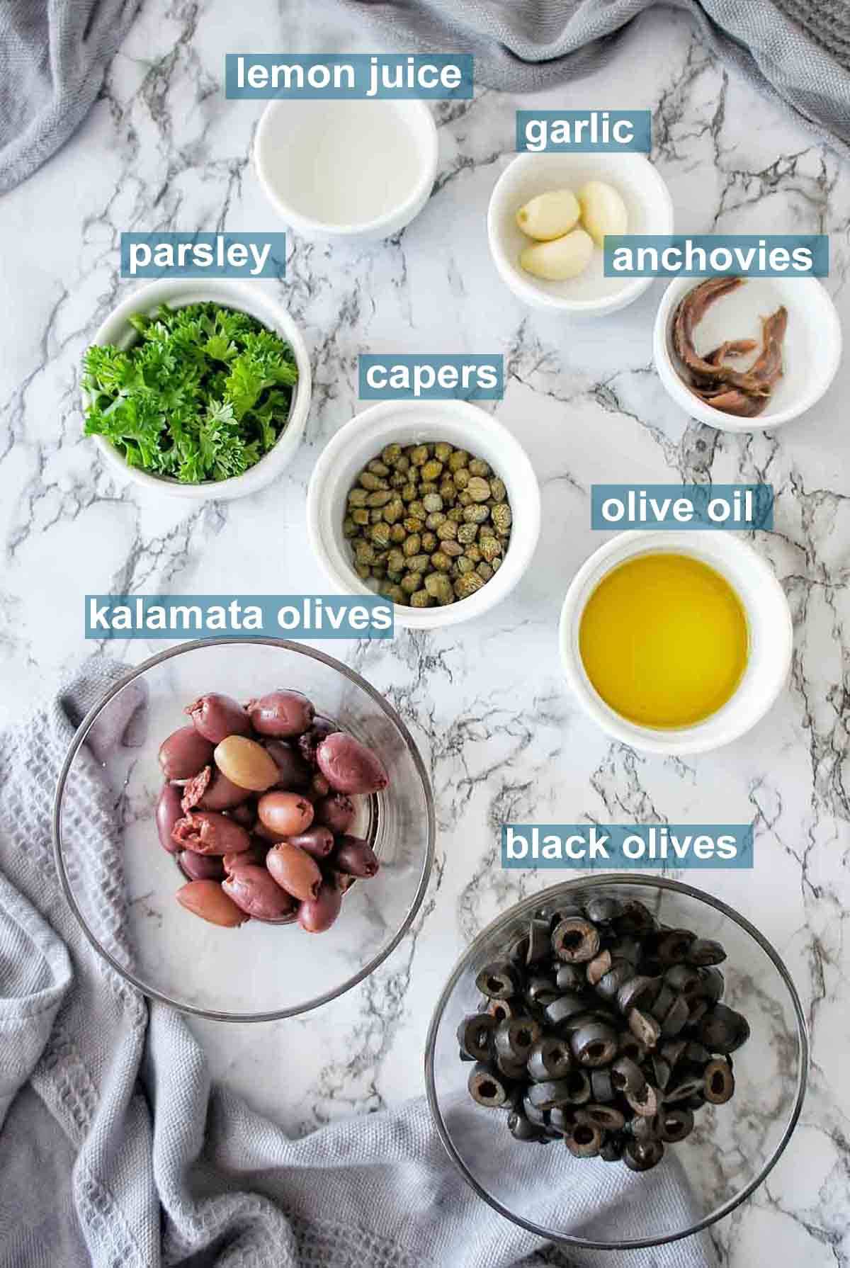 Ingredients for black olive tapenade on marble background with text over lay