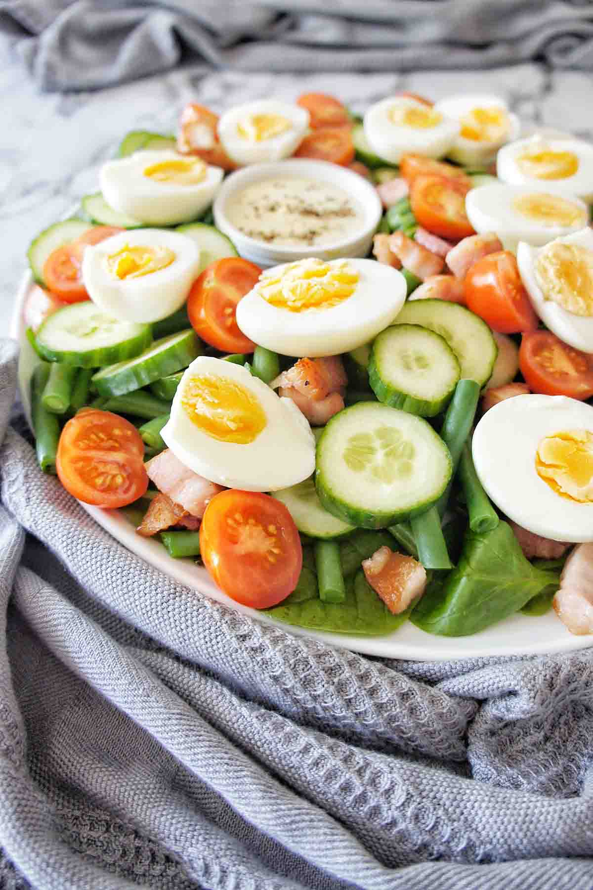 Salad with egg on top on a white plate