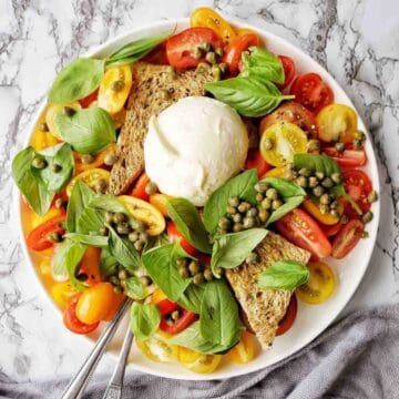 Tomato Burrata Salad on a white plate with capers