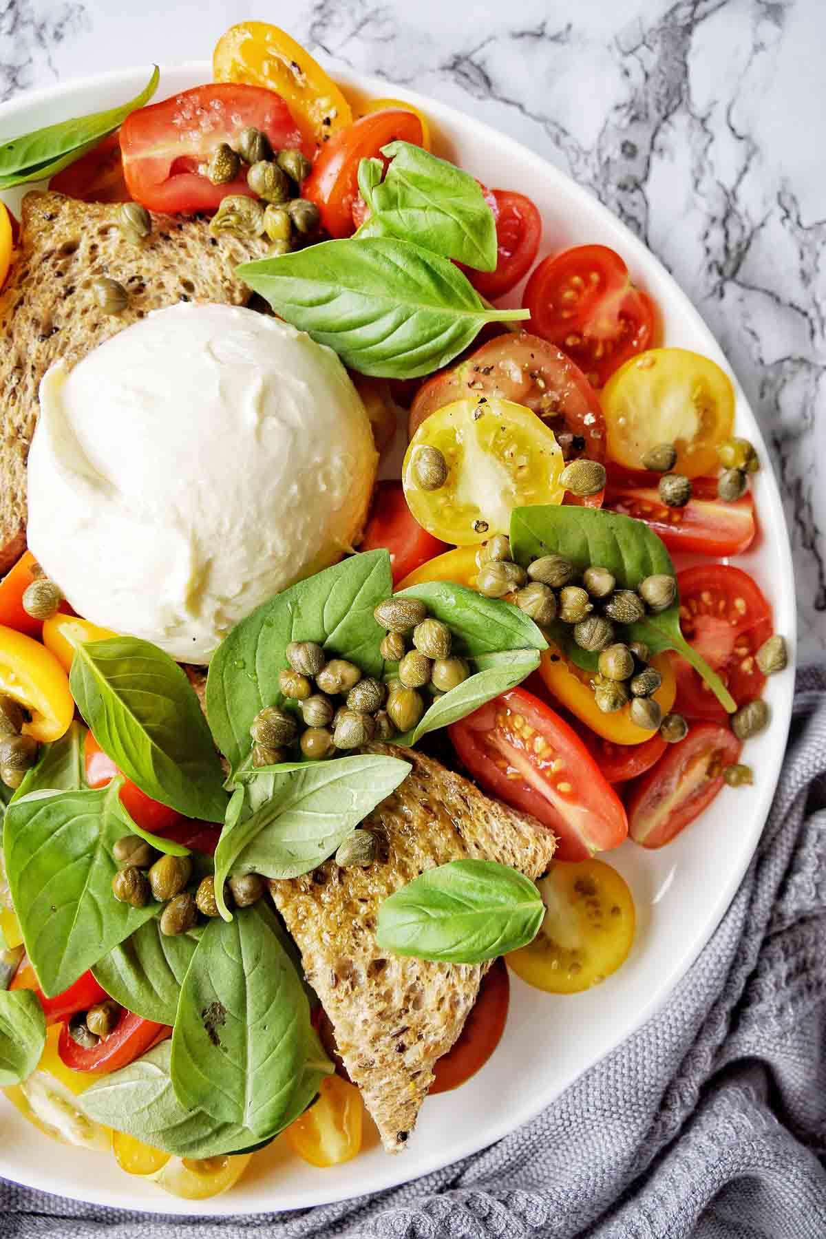 Burrata Salad with basil and capers on a white plate