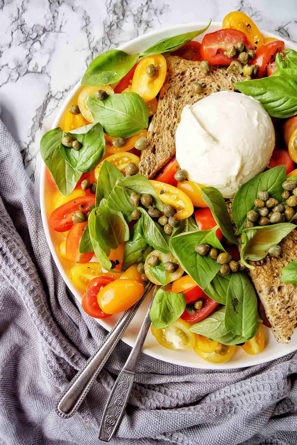 Burrata Salad on a white plate with serving utensils