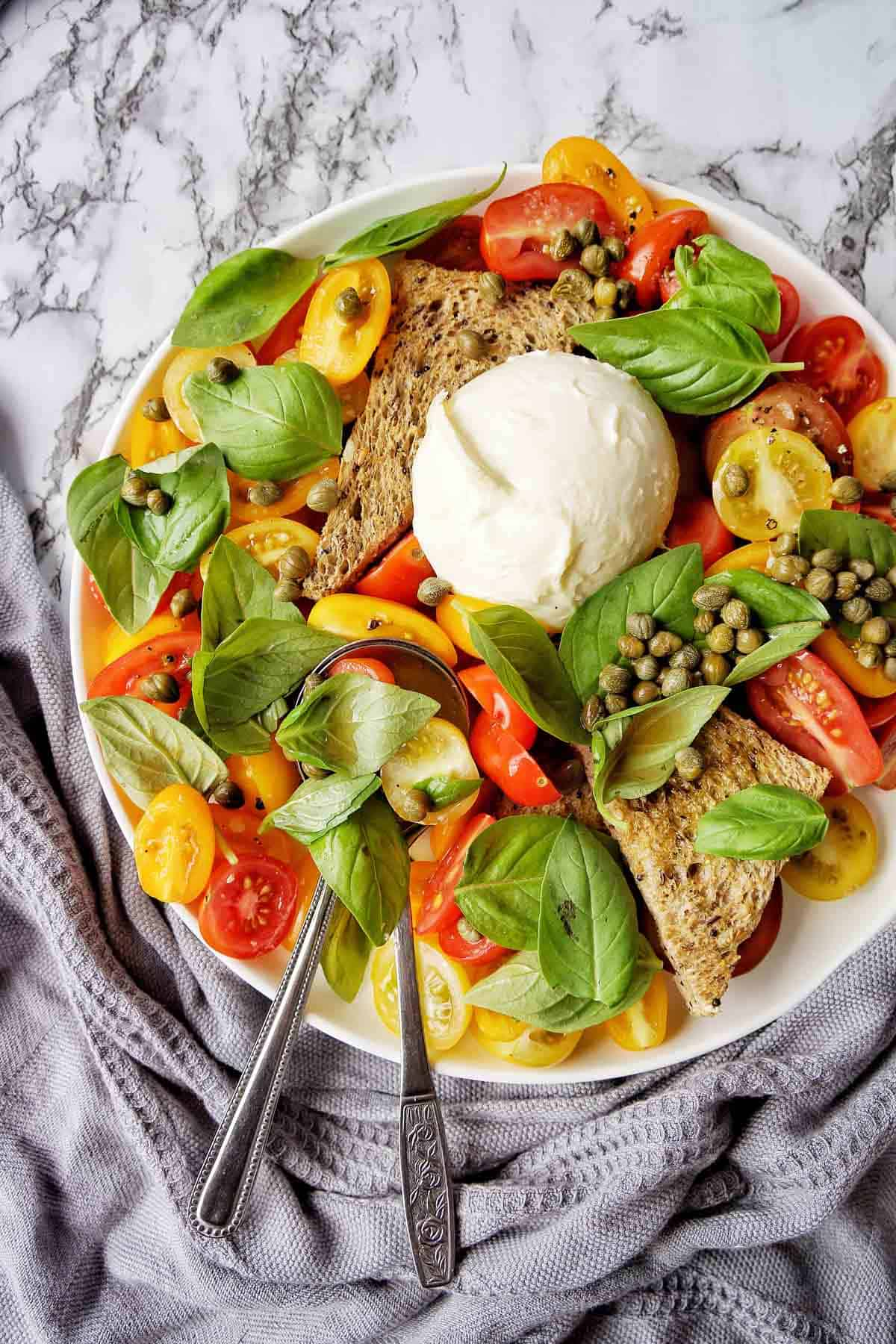 Burrata Salad with wholemeal toast points on white plate