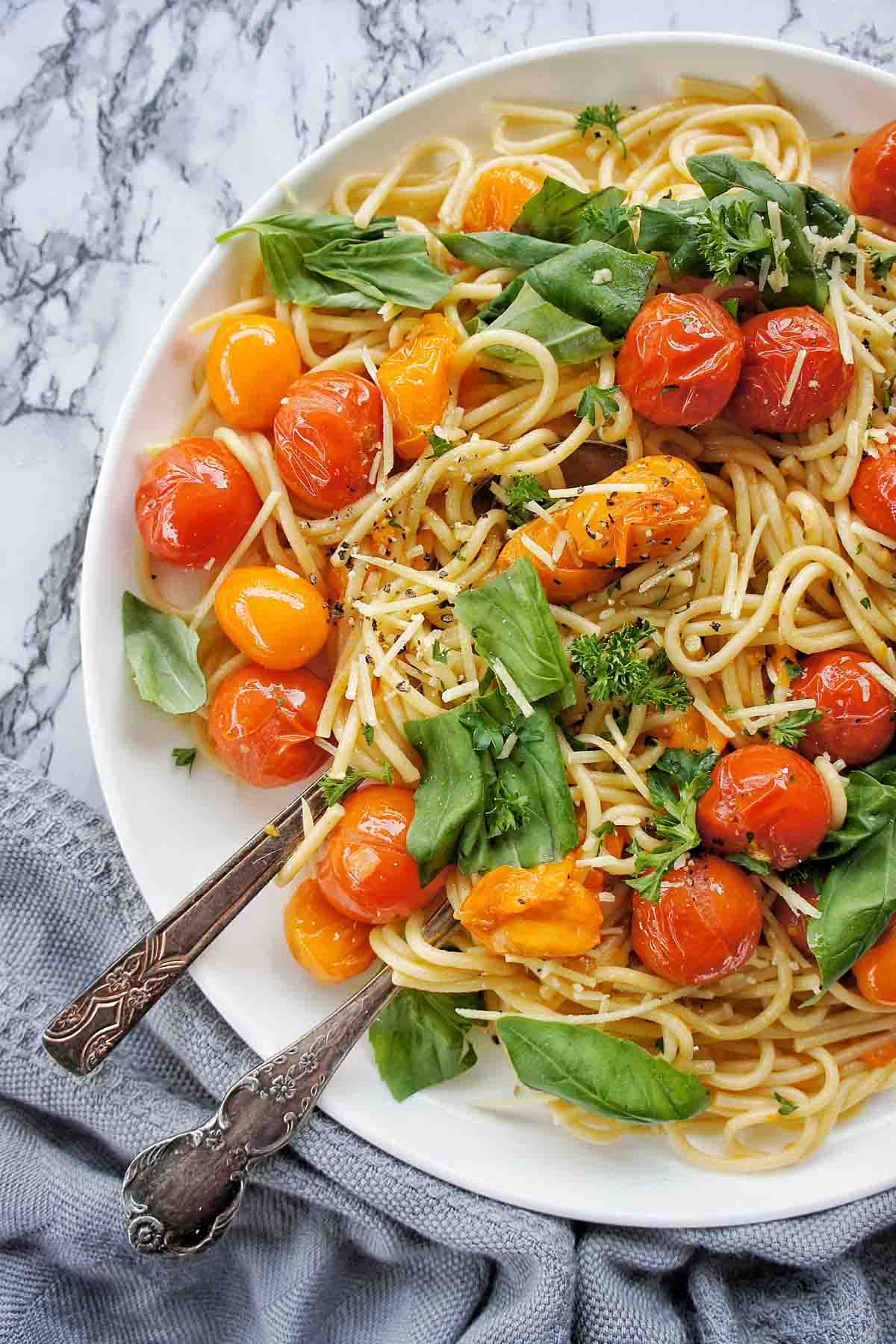Burst Cherry Tomato Pasta on a white plate with basil leaves