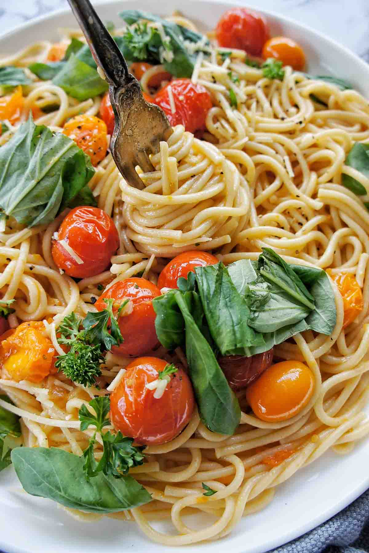 Fork with pasta twirled around it on a plate with cherry tomatoes and basil