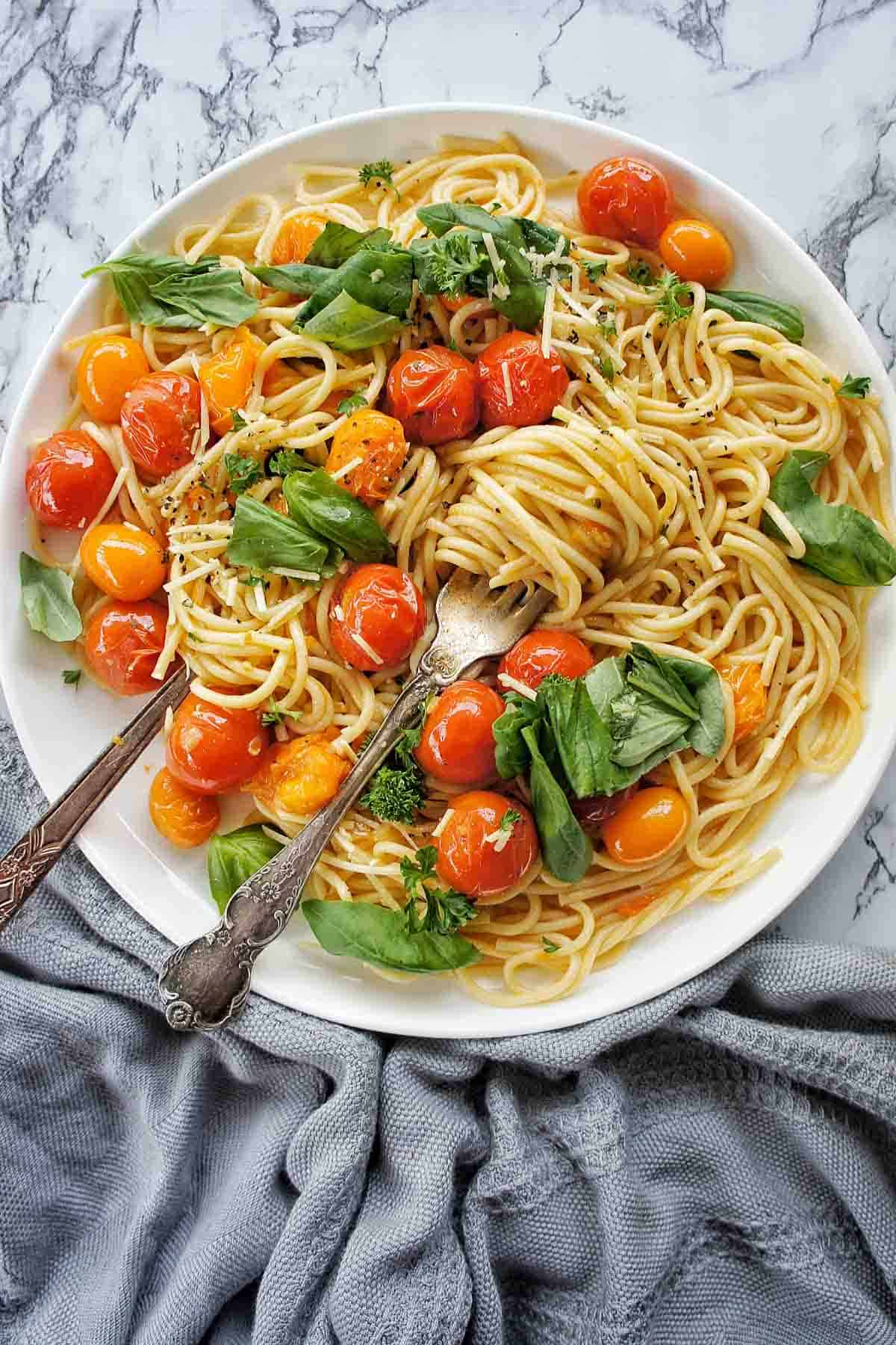 Burst Cherry Tomato Pasta on a blue plate with grey napkin