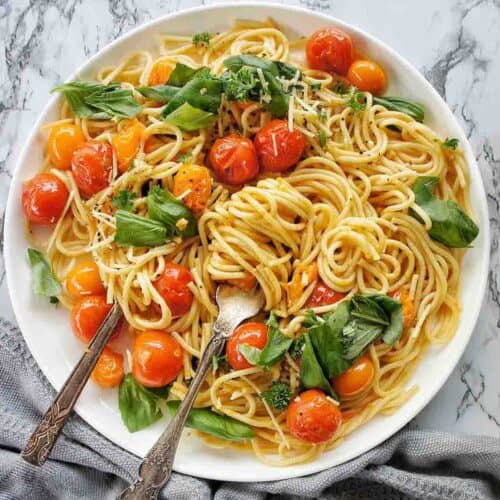 Burst Cherry Tomato Pasta on a white plate with spoon and fork in pasta