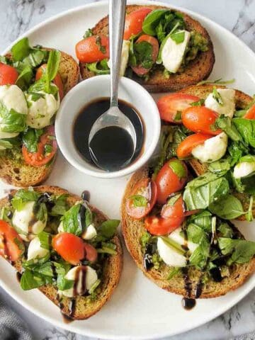 Caprese Bruschetta on a white plate with small bowl of balsamic glaze
