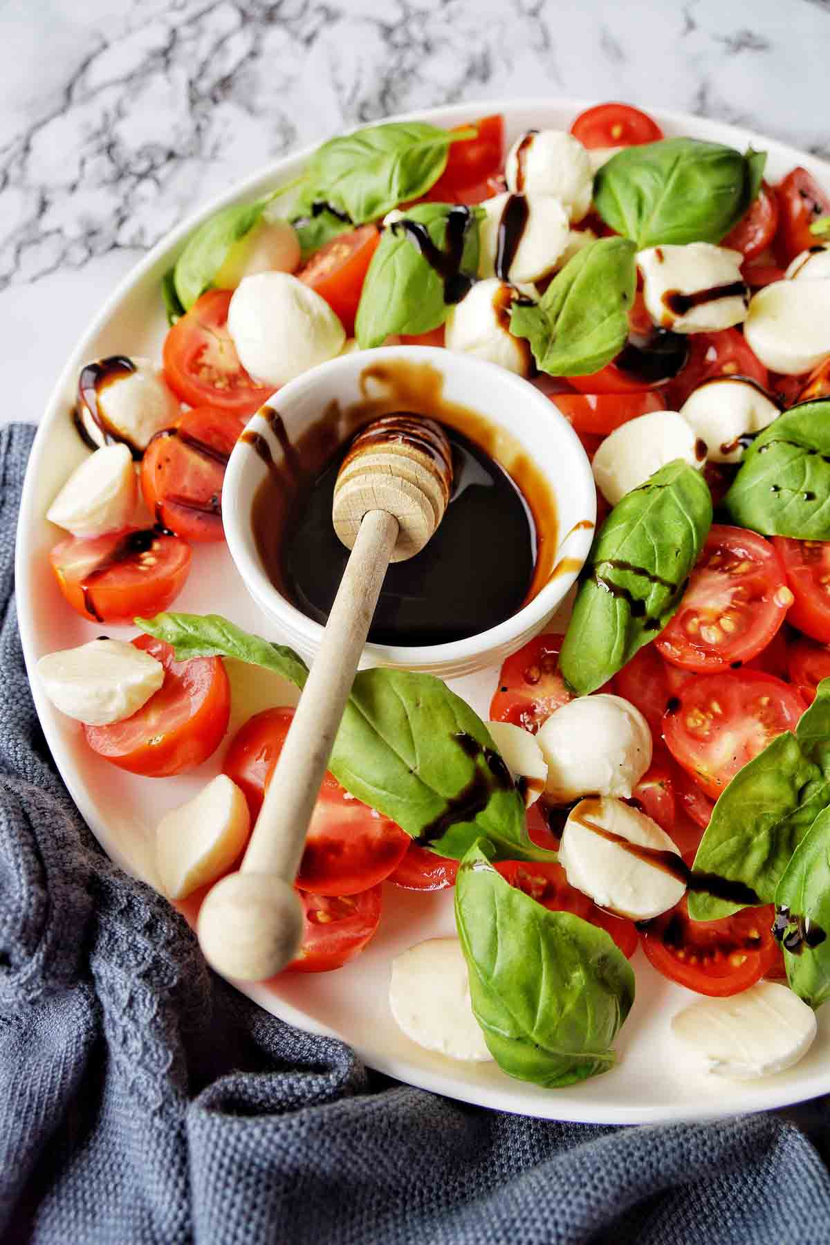 Small server in bowl on balsamic glaze on a white plate with caprese salad