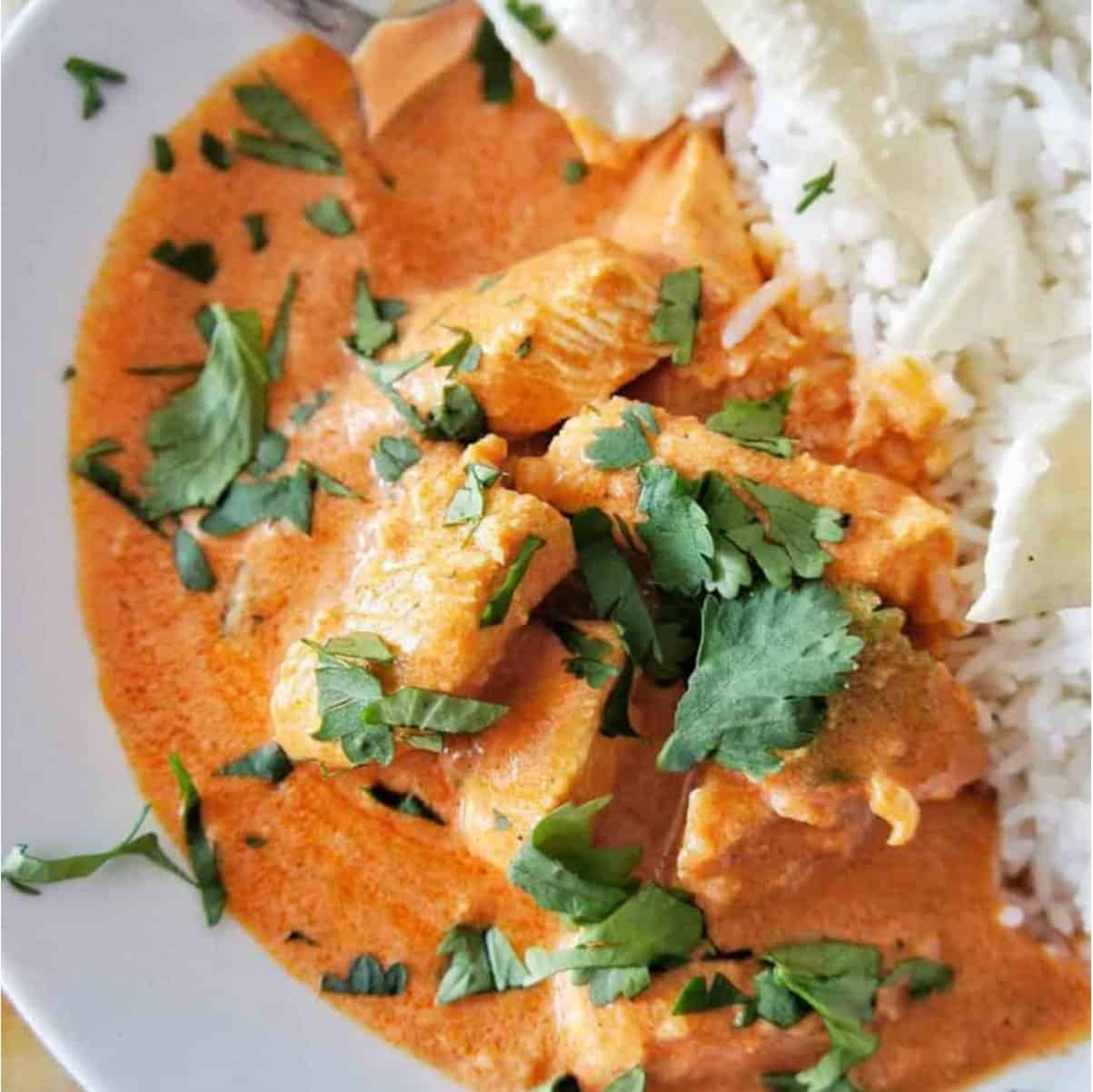 Butter Chicken with rice in a white bowl