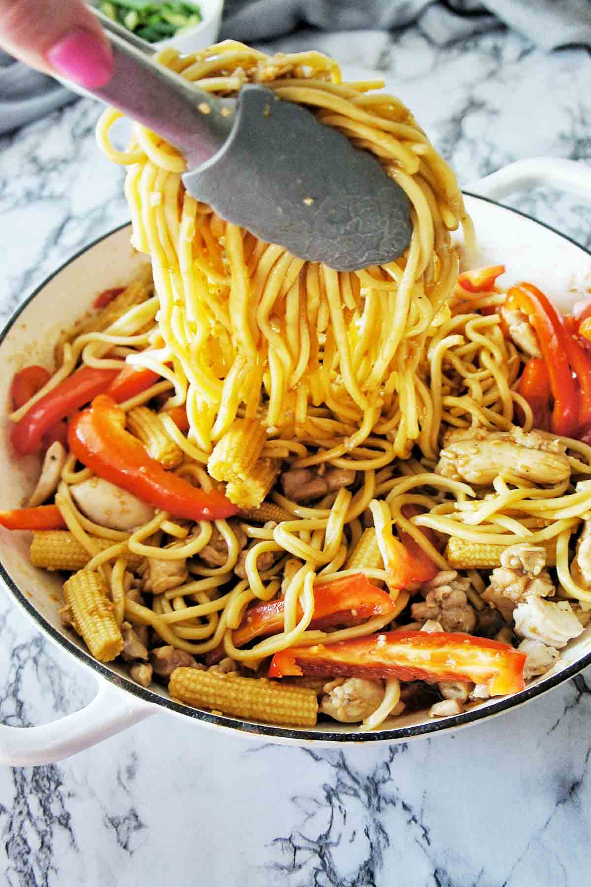 Hokkien Noodles being added to fry pan with chicken and vegetables
