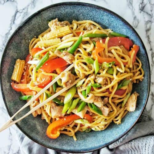 Chicken Noodle Stir Fry in a blue bowl with a pair of wooden tongs