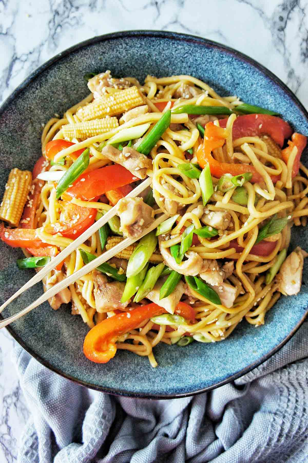 Chicken Noodle Stir Fri in a blue bowl with wooden tongs