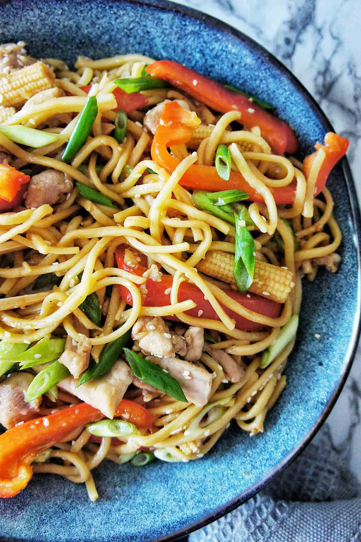 Chicken Noodle Stir Fry with capsicum and corn spears in a blue bowl