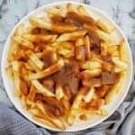 Chips and gravy on a white plate