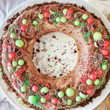 Chocolate Ripple Wreath cake with red and green toppings on a white cake platter