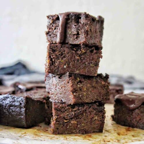 Chocolate Zucchini Brownies stack with icing dripping down from the top