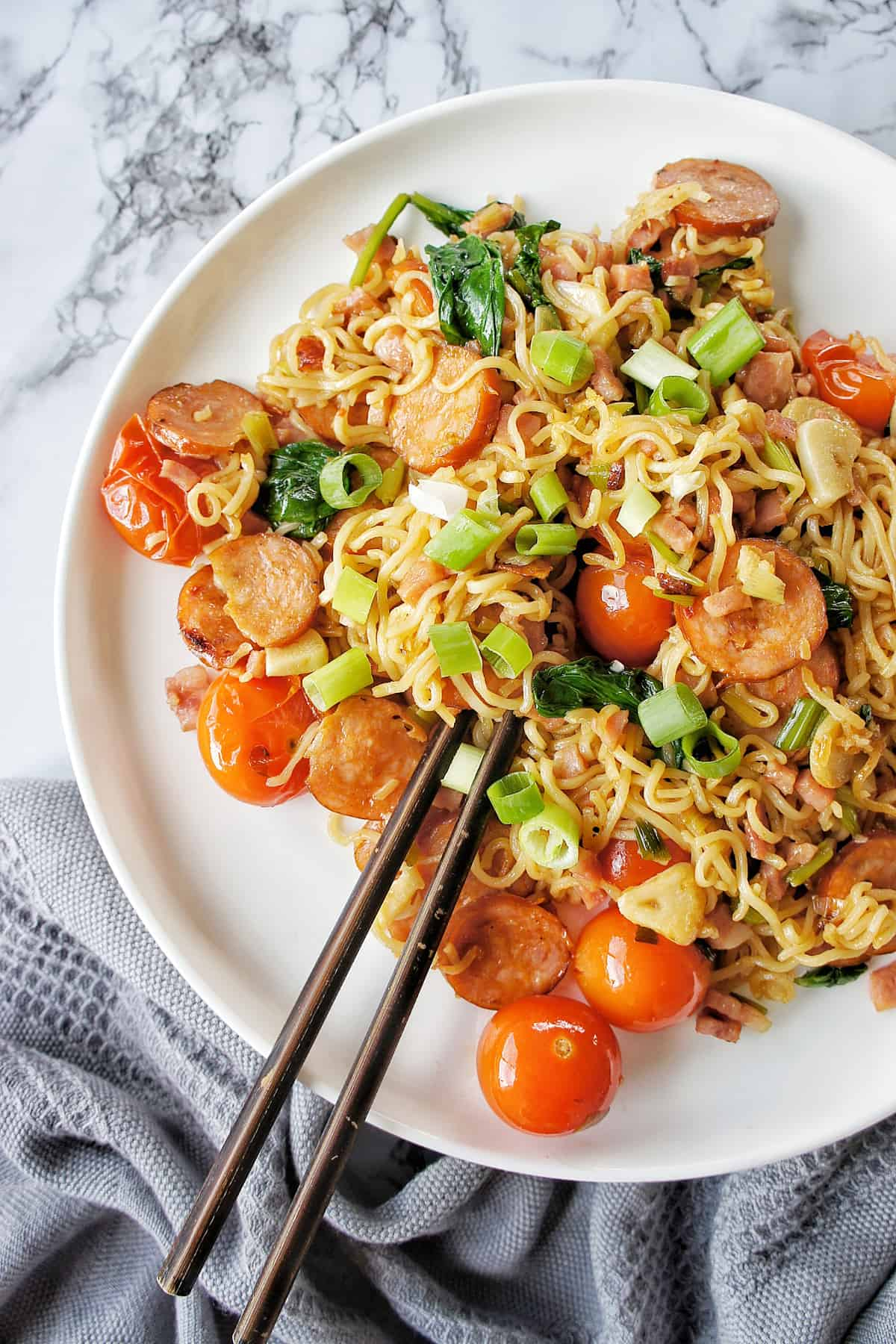 Chorizo Noodles on a white plate with brown chopsticks