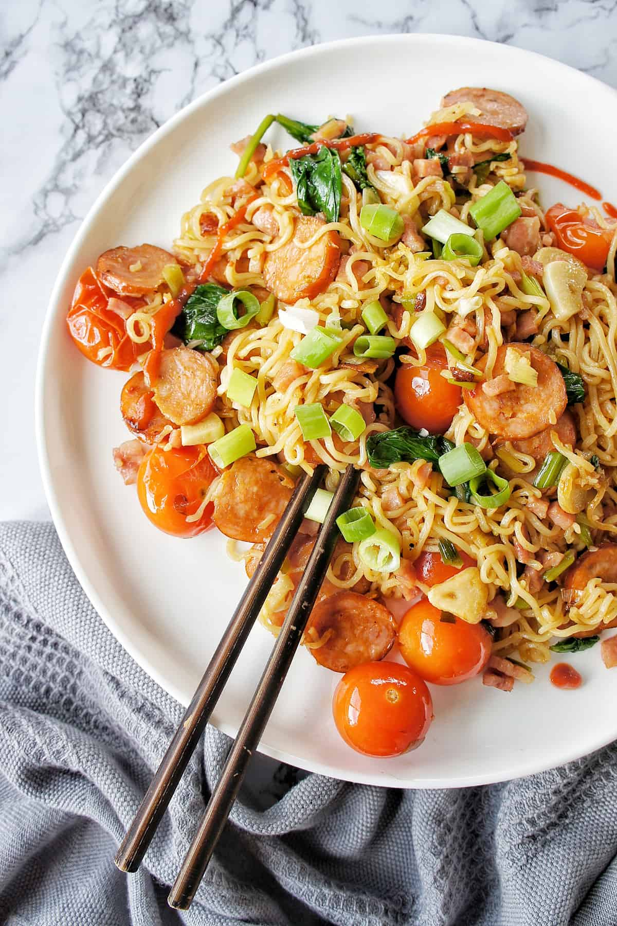 Chorizo Noodles on a white plate with wooden chopsticks