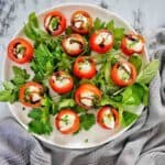 Cold Stuffed Tomatoes on green herbs on white plate