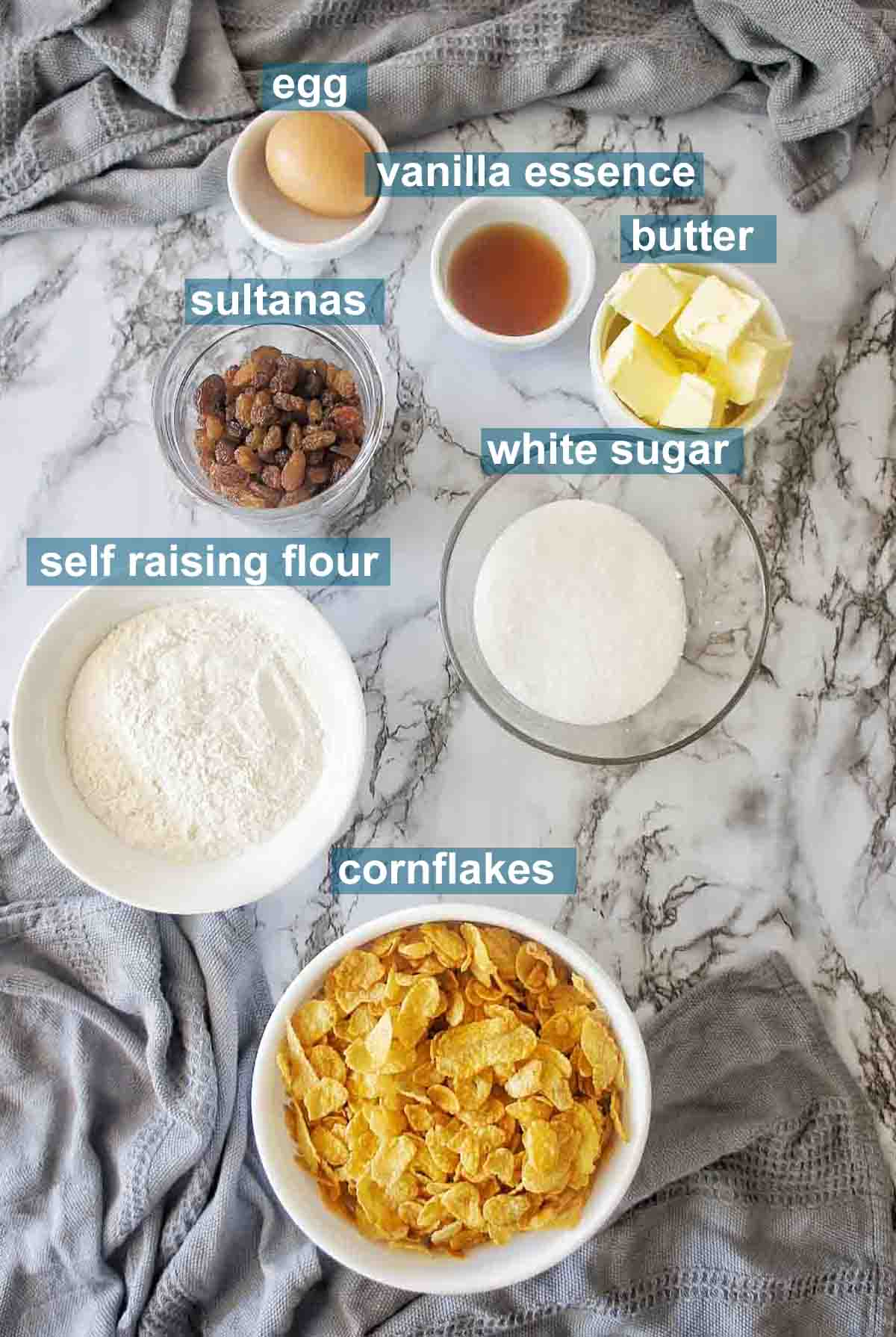 Cornflake biscuit ingredients set out on marble background with text over lay