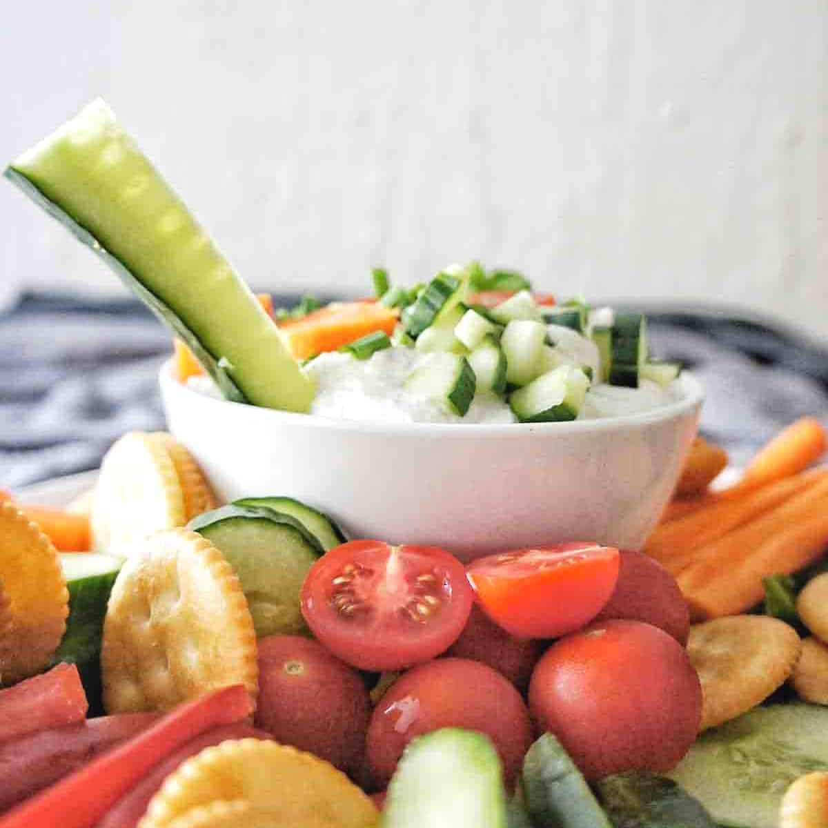 Long cucumber slice sticking out of small bowl of dip with crackers and vegetables around it