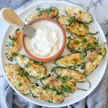 Jalapeno poppers on a white plate with a bowl of white dip