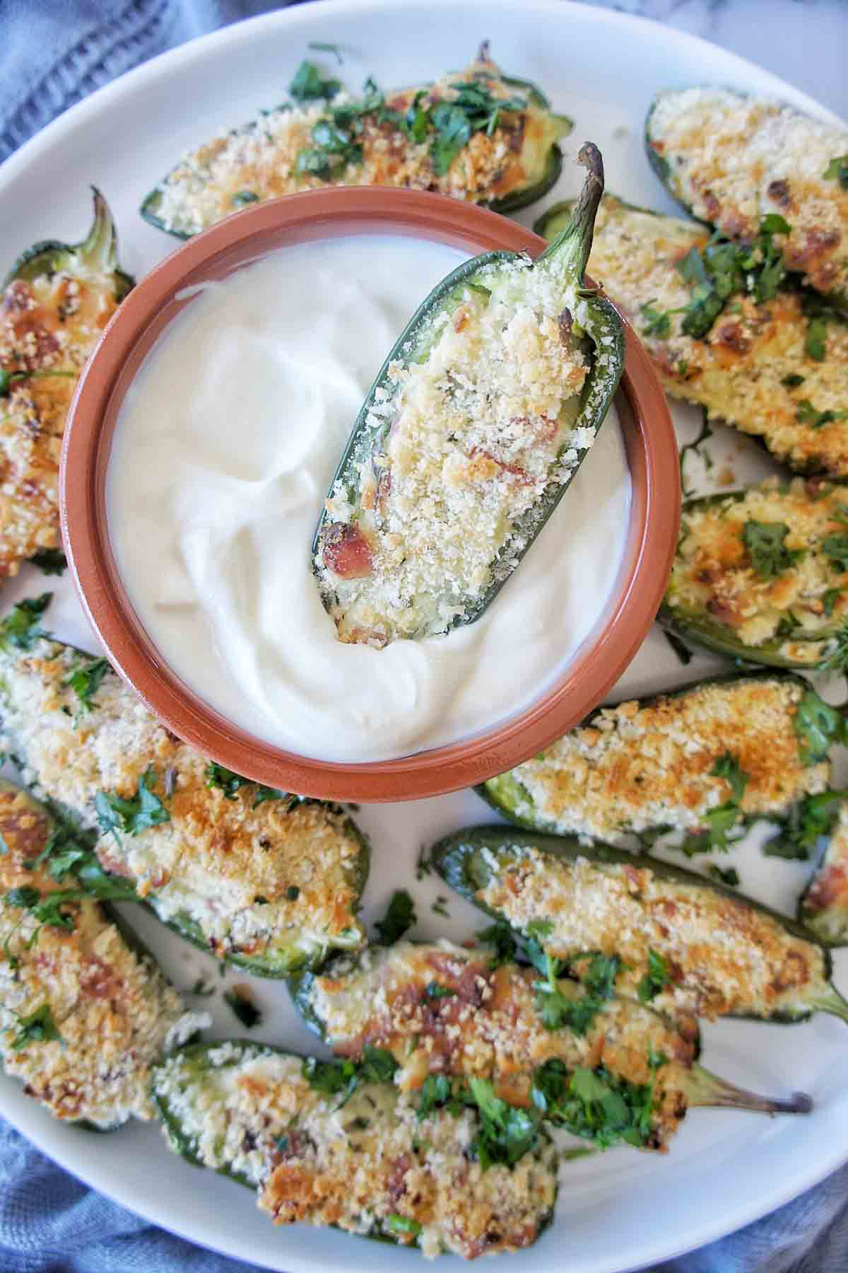 Jalapeno popper being dipped into greek yoghurt on large platter