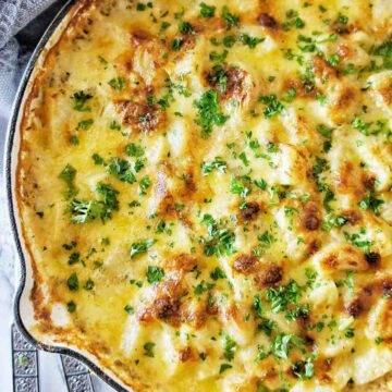 Creamy Garlic Potatoes in a white skillet with servers to the left