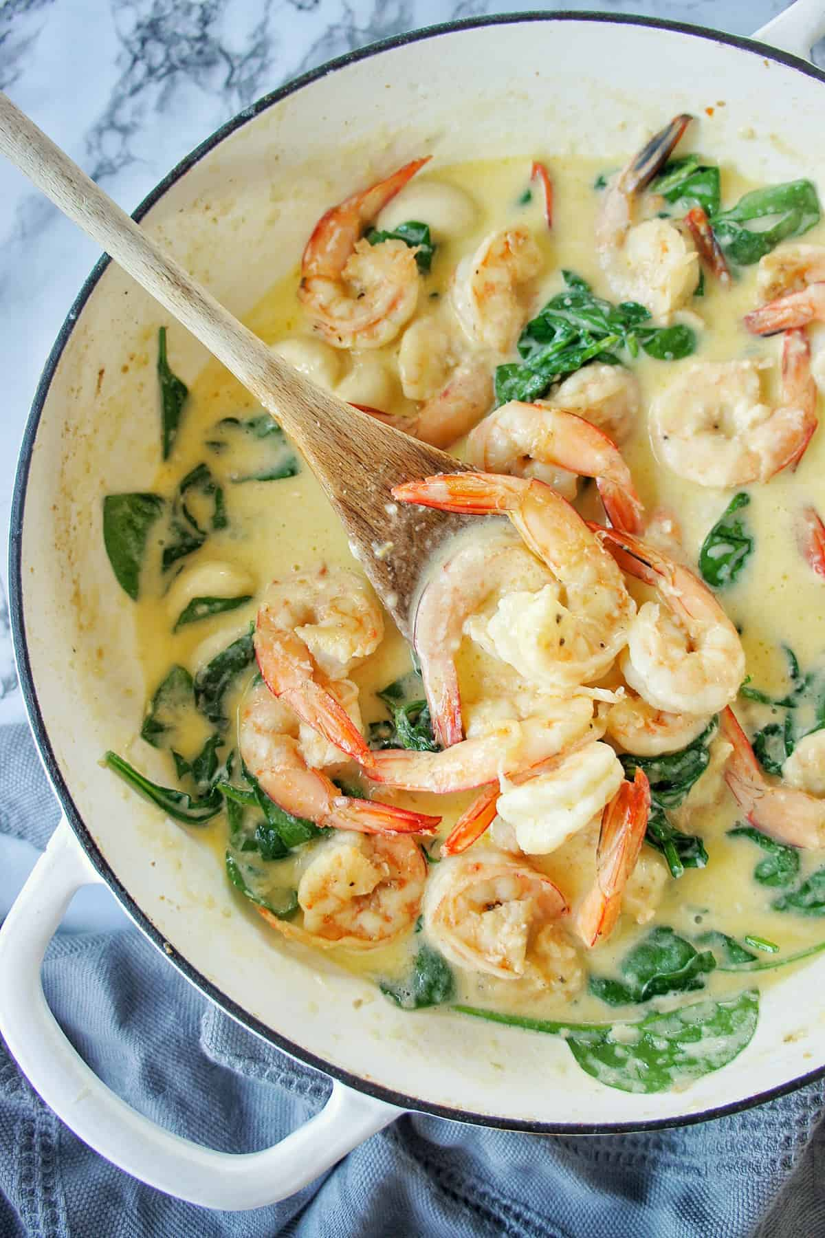 Creamy Garlic Prawns in a white pan with wooden spoon
