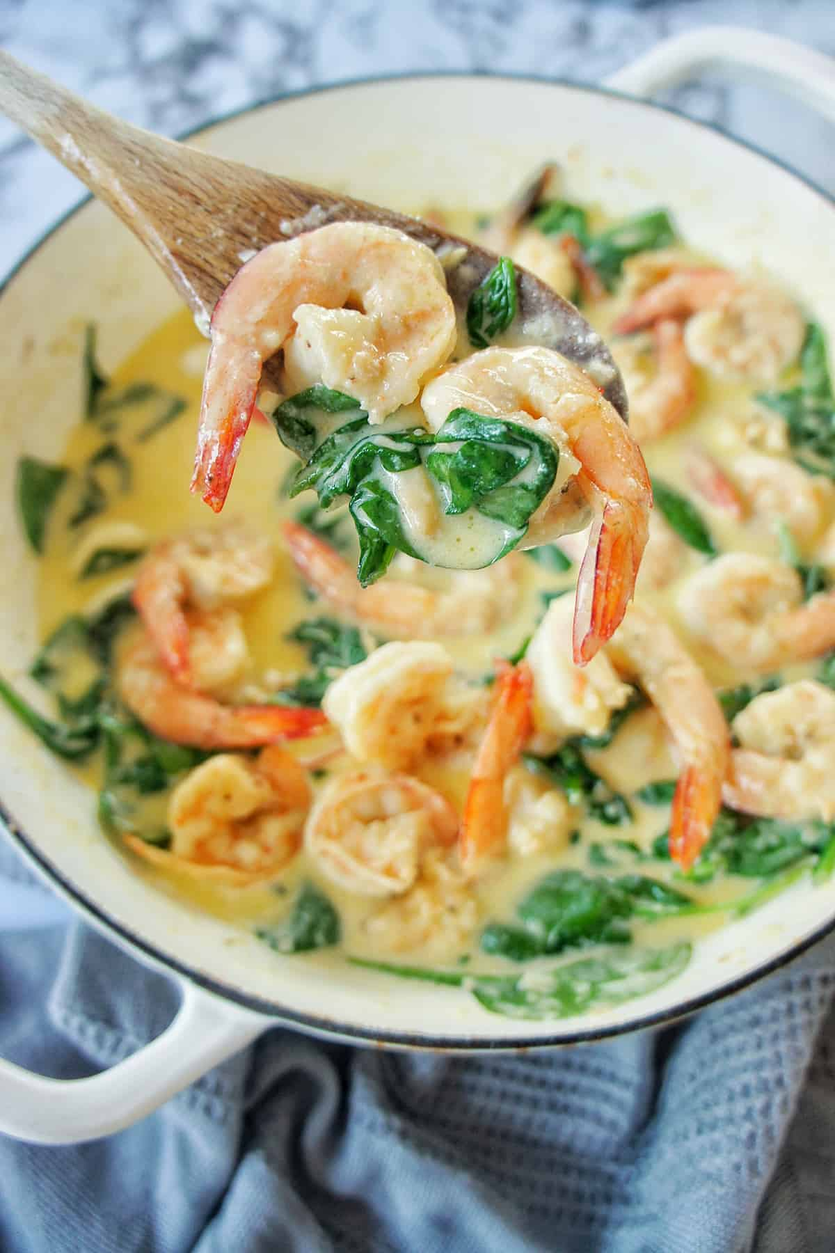 Creamy Garlic Prawns in a wooden spoon above dish of the same