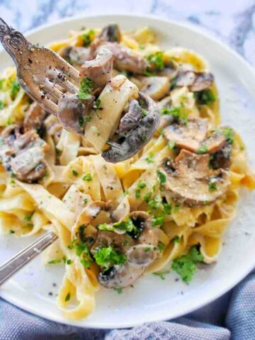 Creamy Mushroom Tagliatelle on a white plate with a fork being twirled