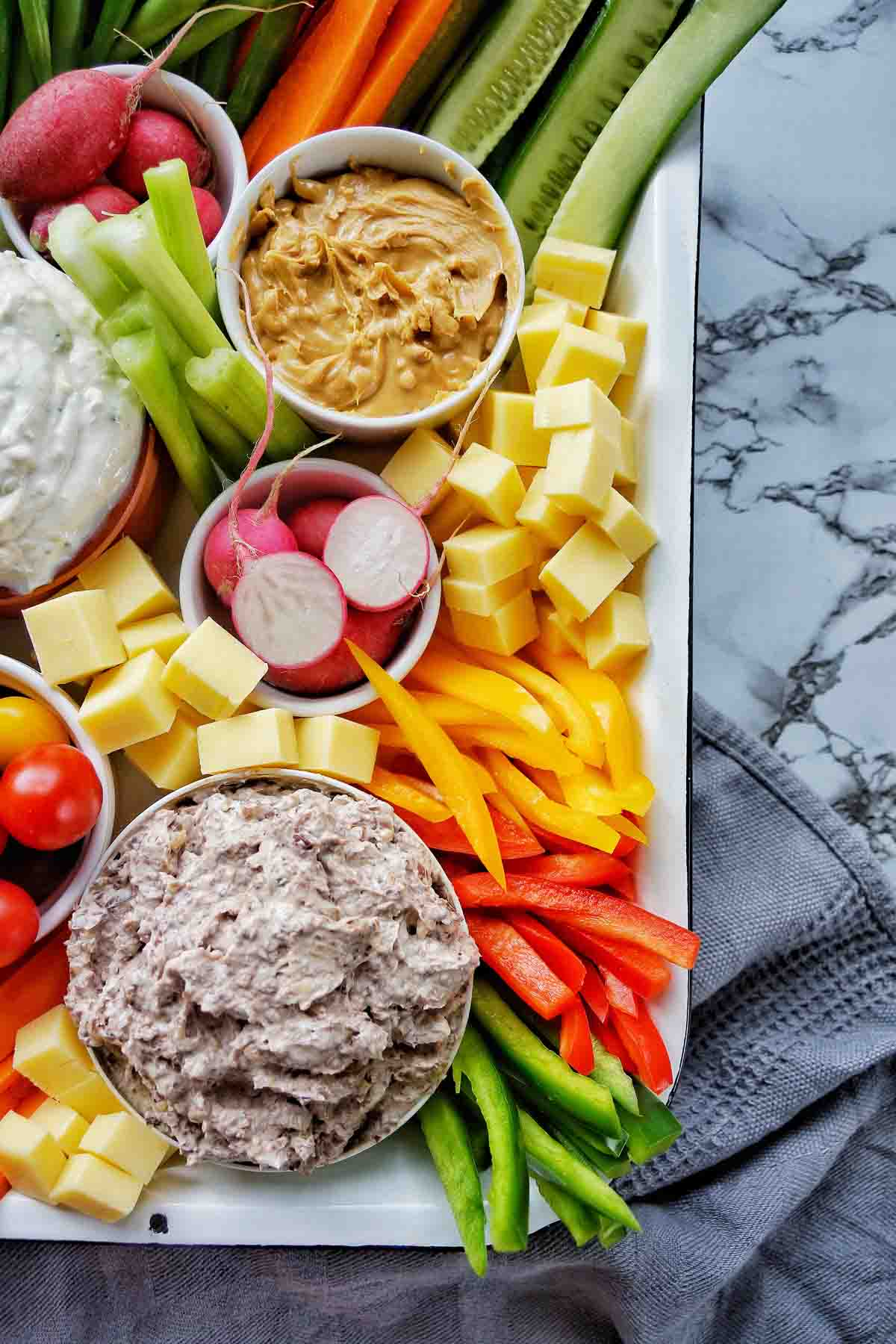 Raw vegetables dips and cheese in white baking tray for grazing board ideas