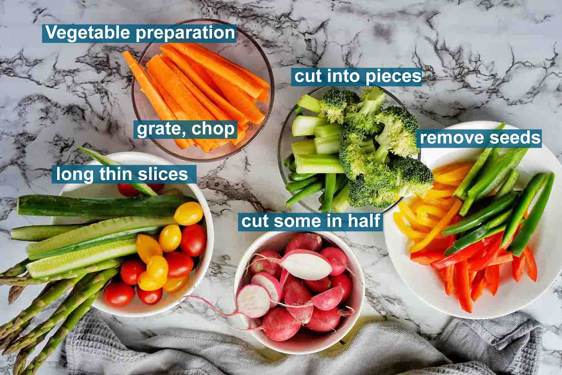 Vegetables prepped for crudite platter in small assorted bowls